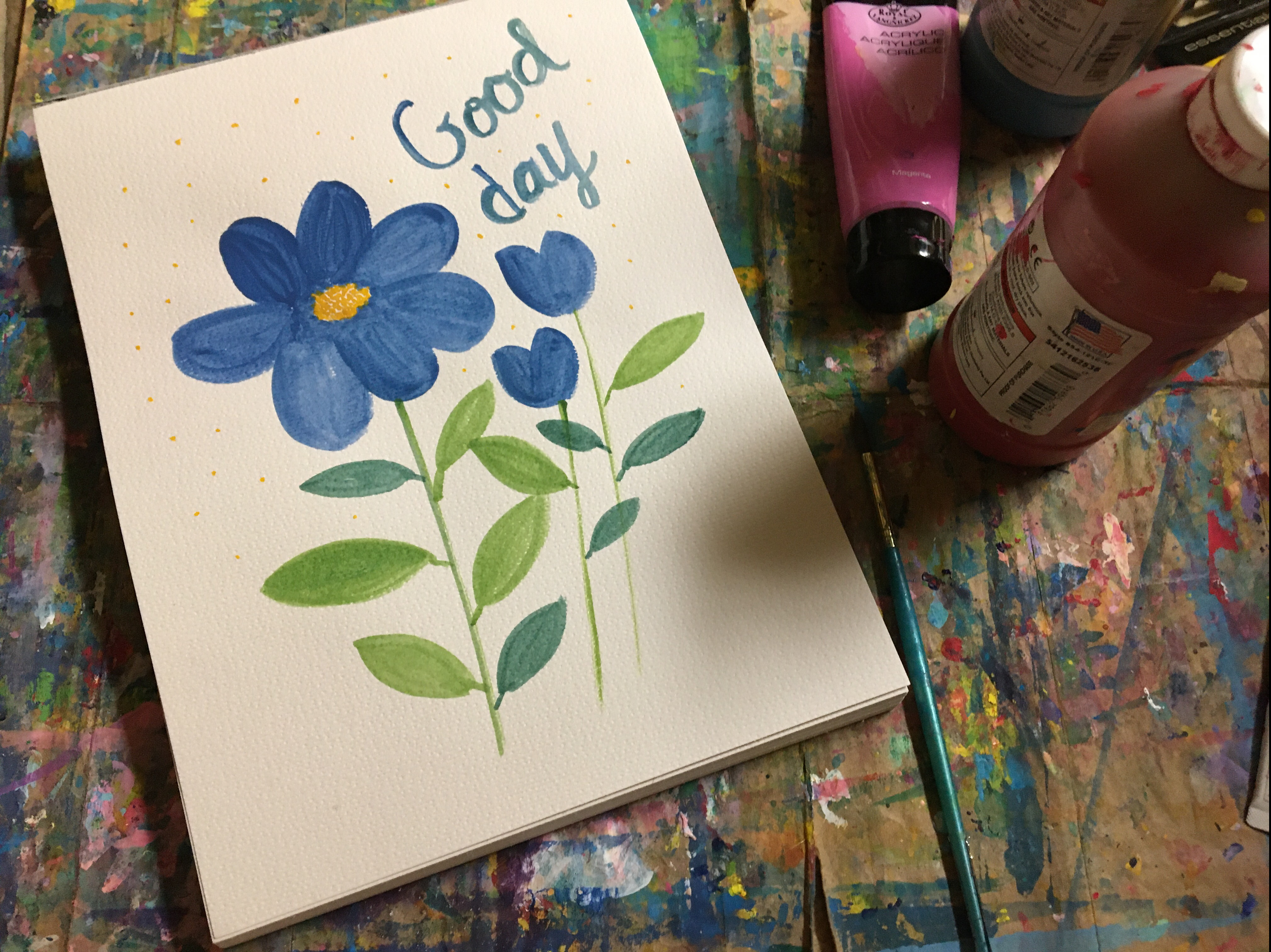 three blue flowers with the a quote good day
